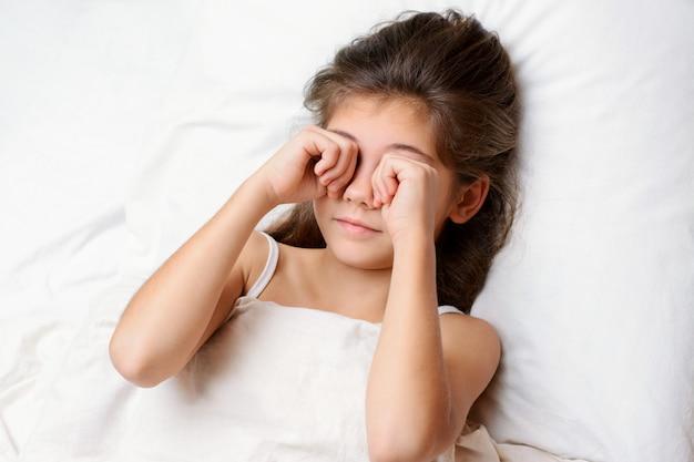 Slaperig mooi klein kind wrijft haar ogen in de ochtend