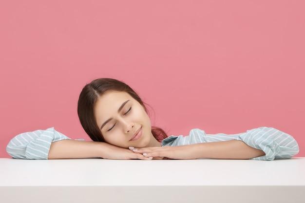 Slaperig student meisje in gestreept blauw shirt vreedzaam dutten tijdens de les op de universiteit, gezicht op haar handen kussen, ogen gesloten houden. mensen, levensstijl, slaap, vermoeiend, leren en onderwijs