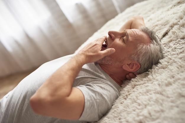 Slaperig uitgeput oudere man gaapt in slaapkamer.