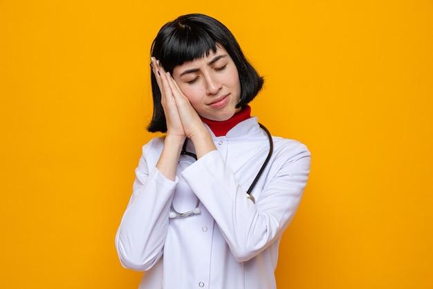 Slaperig, vrij kaukasisch meisje in doktersuniform met stethoscoop legt hoofd op handen