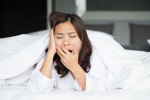 Slaperige aziatische vrouw die in bed thuis geeuwt
