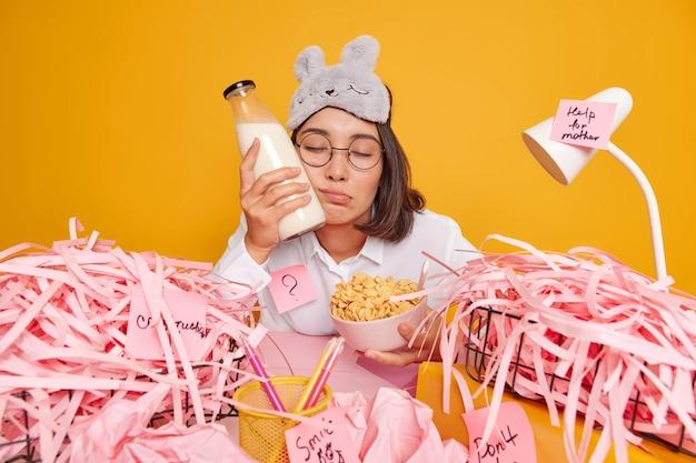 Slaperige aziatische vrouw had niet genoeg slaap houdt fles melkkom met cornflakes besteedt tijd voor cursuswerk poses op desktop draagt slaapmasker op voorhoofd geïsoleerd over gele studiomuur