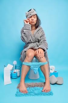 Slaperige aziatische vrouw wordt vroeg in de ochtend wakker en komt in het toilet op het toilet zitten