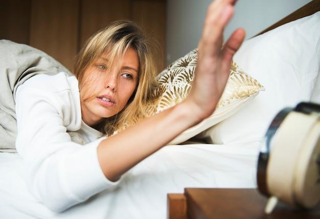 Slaperige blanke vrouw die een alarm uitschakelt
