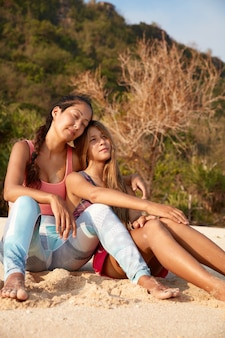 Slaperige dromerige halfbloedvrouwen zitten op het zandstrand