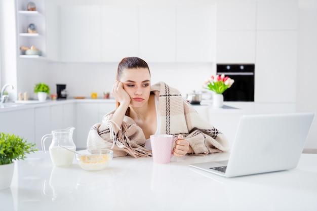 Slaperige huisvrouw dame ontbijten koffie drinken kijken notitieboekje