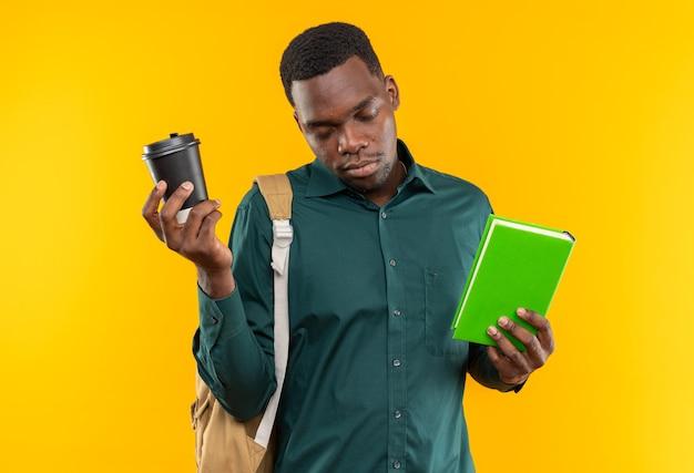 Slaperige jonge afro-amerikaanse student met rugzak met boek en papieren beker