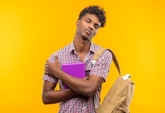 Slaperige jonge afro-amerikaanse student met rugzak met boek
