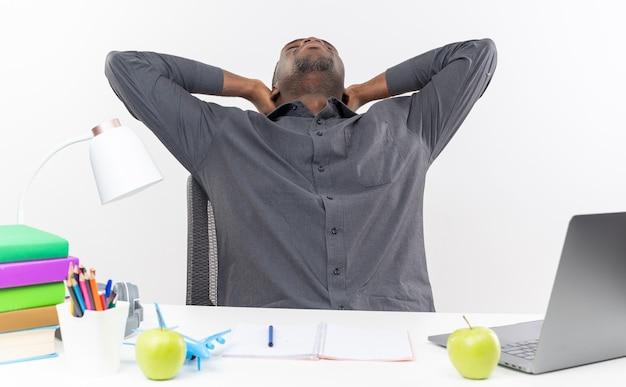 Slaperige jonge afro-amerikaanse student zit aan een bureau met schoolhulpmiddelen die handen op zijn hoofd zetten