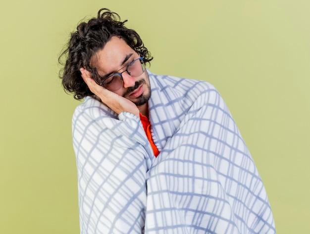 Slaperige jonge blanke zieke man met bril gewikkeld in plaid doet slaapgebaar geïsoleerd op olijfgroene achtergrond