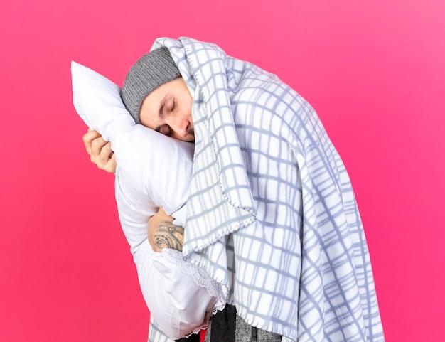 Slaperige jonge blanke zieke man met muts gewikkeld in plaid zet hoofd op kussen geïsoleerd op roze muur met kopie ruimte