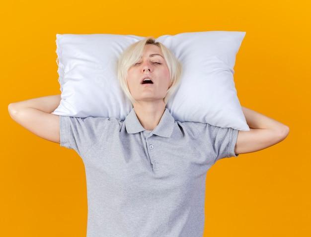 Slaperige jonge blonde zieke slavische vrouw houdt kussen achter hoofd geïsoleerd op oranje muur met kopie ruimte