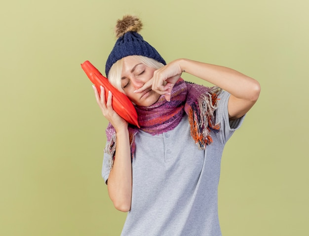 Slaperige jonge blonde zieke slavische vrouw met muts en sjaal veegt neus met vinger af en zet hoofd op warmwaterkruik geïsoleerd op olijfgroene muur met kopie ruimte