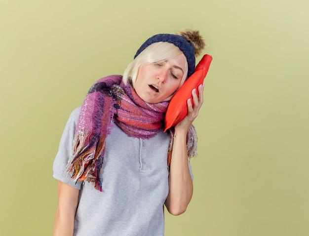 Slaperige jonge blonde zieke slavische vrouw met muts en sjaal zet warmwaterkruik op gezicht geïsoleerd op olijfgroene muur met kopie ruimte