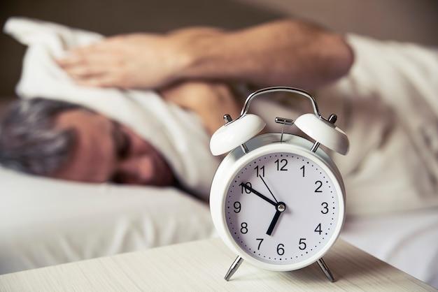 Slaperige jonge man die oren met kussen omhelst als hij wekker in bed kijkt. slapende man die vroegtijdig wakker wordt door de wekker. gefrustreerde man luisteren naar zijn wekker terwijl hij op zijn bed slaapt