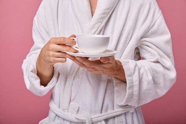 Slaperige jonge man met een kopje koffie in zijn handen