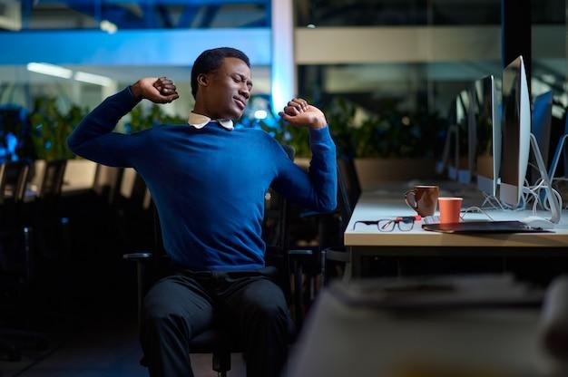 Slaperige jonge manager werkt in nachtkantoor. slaperige mannelijke zakenman, donker zakencentruminterieur, moderne werkplek