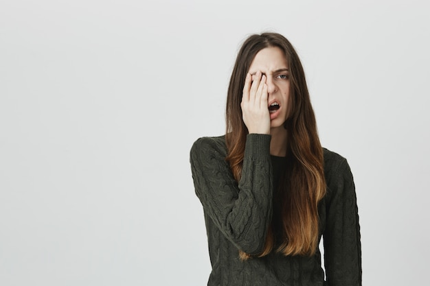 Slaperige jonge vrouw facepalm en geeuw uitgeput