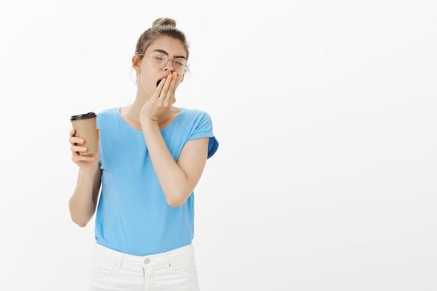 Slaperige jonge vrouw in glazen koffie drinken en geeuwen, 's ochtends kopje cafeïne
