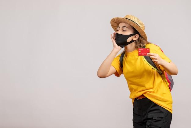 Slaperige jonge vrouw met een zwart masker die kaart op wit houdt