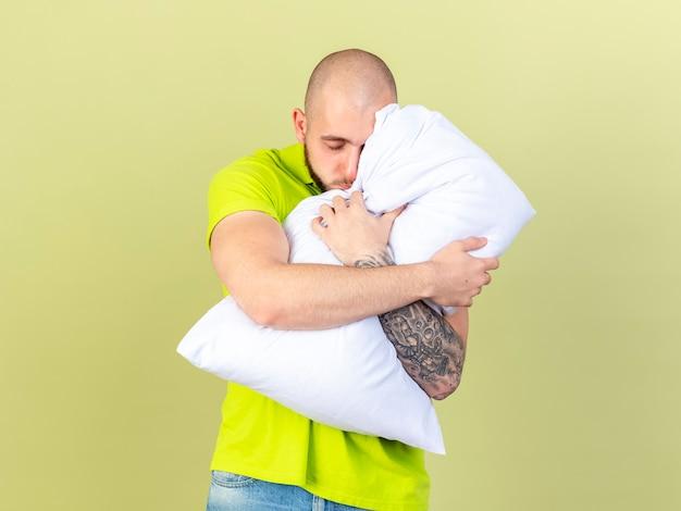 Slaperige jonge zieke man knuffels kussen geïsoleerd op olijfgroene muur