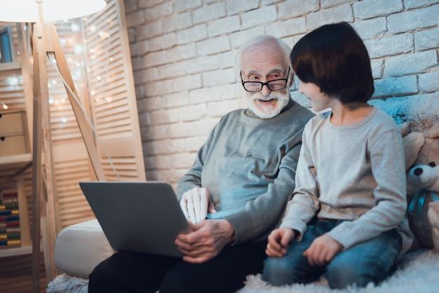 Slaperige jongenszitting dichtbij het werken laptop opa