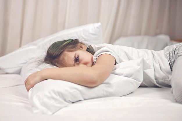 Slaperige kinderen in pyjama die in bed liggen en 's avonds worstelen om te slapen