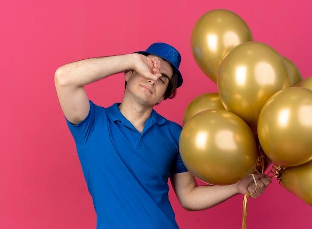 Slaperige, knappe blanke man met een blauwe feesthoed zet zijn vuist op het voorhoofd en houdt heliumballonnen vast