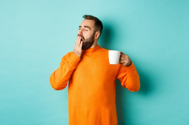 Slaperige knappe man koffie drinken en geeuwen, staande in oranje trui tegen licht turkooizen muur