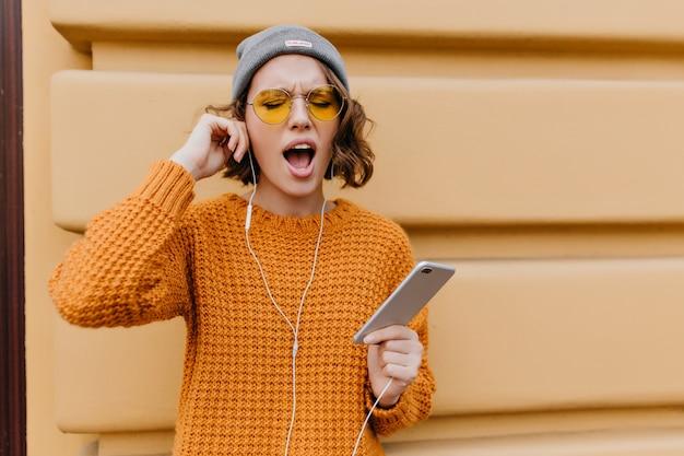 Slaperige krullende vrouw in trui die in de ochtend gaat lopen en oortelefoons draagt