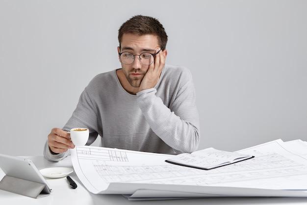 Slaperige man drinkt koffie terwijl hij zich moe voelt, werkt de hele dag aan blauwdrukken, heeft vermoeidheidsuitdrukkingen
