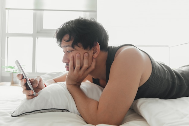 Slaperige man gebruikt smartphone terwijl hij op het bed ligt.