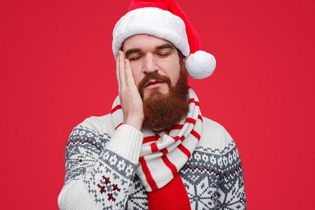 Slaperige man in santa hat sluiten ogen moe