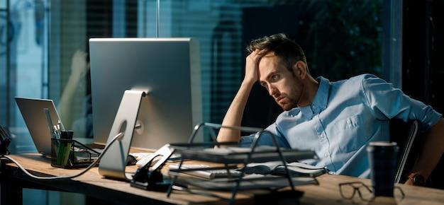 Slaperige man werkt overuren in kantoor
