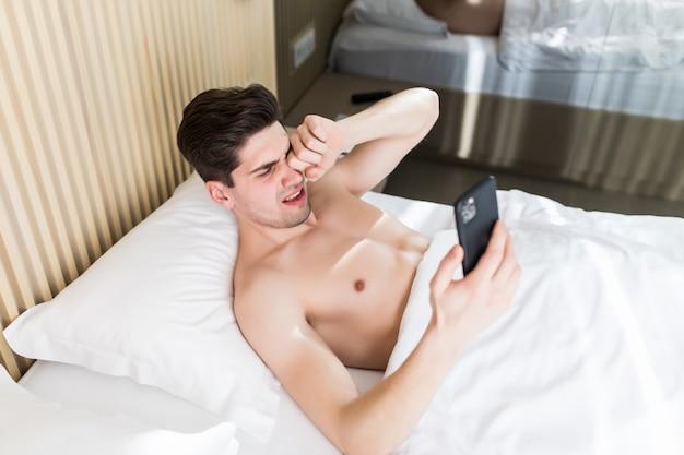 Slaperige mens die in ochtendbed liggen met telefoon die app gebruiken of nieuwsfeed lezen. man wordt wakker van telefoonalarm of telefoontje.
