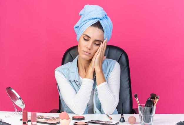 Slaperige, mooie blanke vrouw met gewikkeld haar in een handdoek zittend aan tafel met make-uptools die het hoofd op haar handen leggen