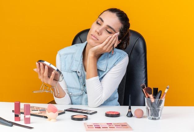 Slaperige, mooie kaukasische vrouw die aan tafel zit met make-upgereedschap, hand op haar gezicht met make-upborstel en spiegel