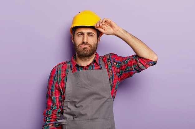 Slaperige, overwerkte arbeider, moe van reparatie of constructie, draagt een beschermende helm, een geruit overhemd en een schort, moet het werk afmaken, geïsoleerd op een paarse muur. vermoeidheid mannelijke ingenieur