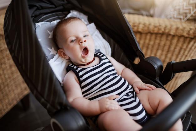 Slaperige schattige kaukasische 6 maanden oude babyjongen zit in de wandelwagen in café en geeuwen.