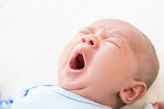Slaperige schattige pasgeboren baby die in bed geeuwt