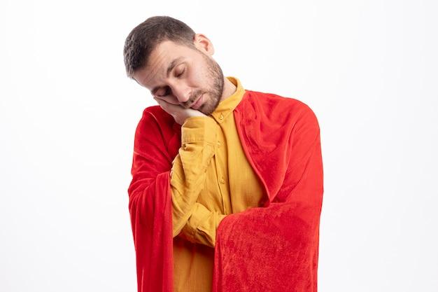 Slaperige superheld man met rode mantel zet hoofd aan kant geïsoleerd op een witte muur