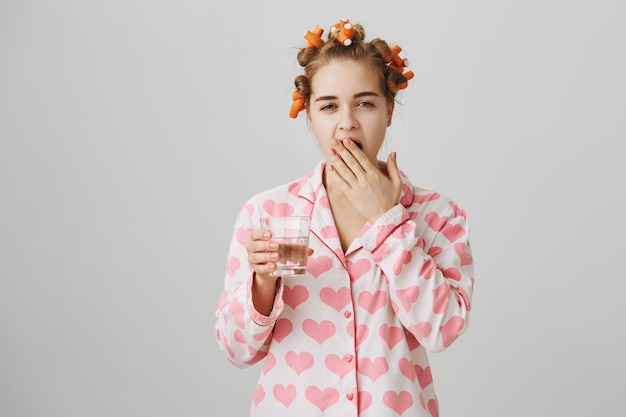 Slaperige tienermeisje in haarkrulspelden en pyjama's geeuwen, met glas water