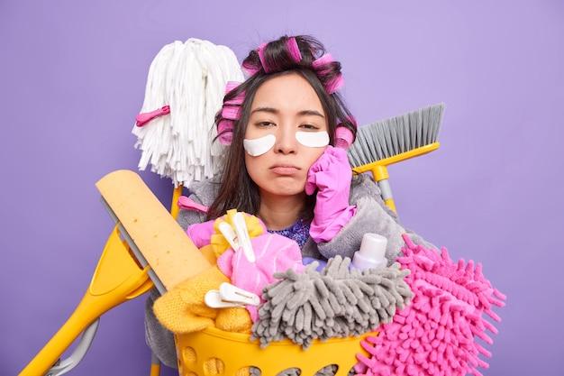 Slaperige, vermoeide aziatische vrouw met krullend kapsel voelt zich uitgeput na het schoonmaken van het huis