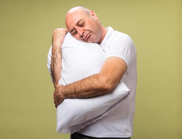 Slaperige volwassen zieke blanke man houden en zetten hoofd op kussen geïsoleerd op olijfgroene muur met kopie ruimte