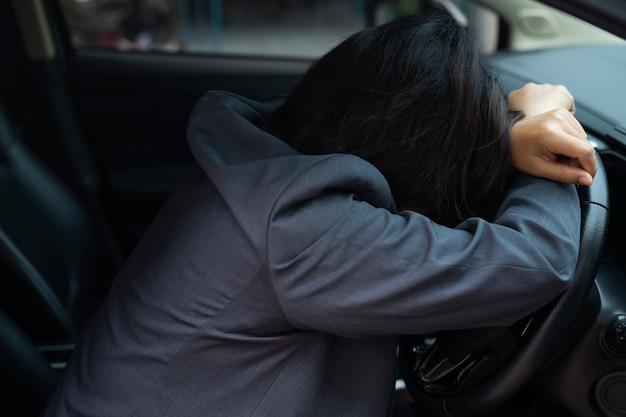 Slaperige vrouw die in slaap valt in auto is gevaarlijk om te rijden