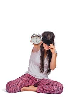 Slaperige vrouw die pyjama's draagt en wekker houdt.