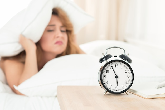 Slaperige vrouw die zich 's ochtends onder het kussen probeert te verstoppen