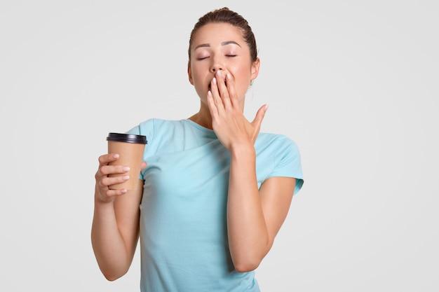 Slaperige vrouw geeuwt, bedekt mond met hand, drinkt warme koffie om zich verfrist te voelen, gekleed in casual blauw t-shirt, geïsoleerd over witte muur. vrouwelijk model met wegwerp koffie.