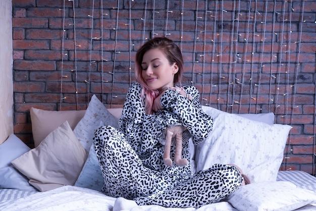 Slaperige vrouw in luipaard pyjama knuffelt haar tildamuis