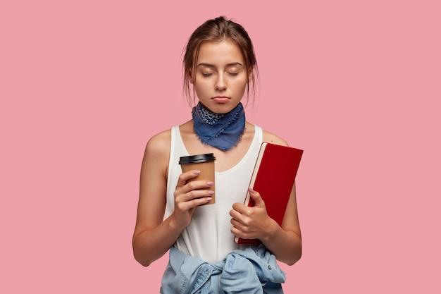 Slaperige vrouw met droevige blik, houdt leerboek vast, houdt de ogen dicht en wil rust hebben